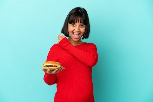 Młoda kobieta w ciąży świętująca zwycięstwo trzymająca burgera na białym tle