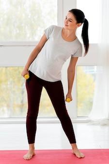 Młoda kobieta w ciąży szkolenia z ciężarami