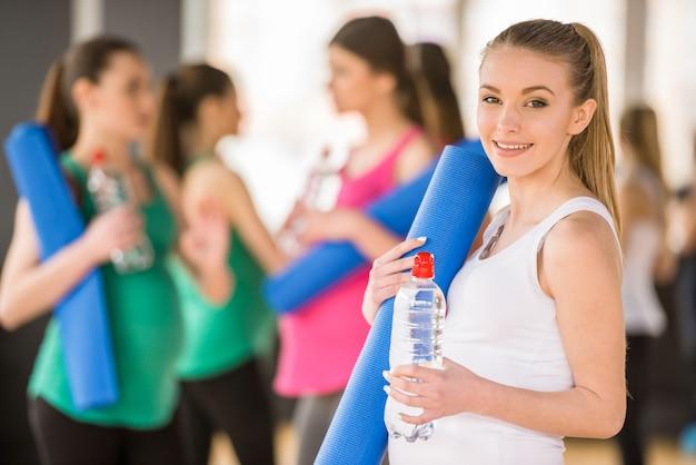 Młoda kobieta w ciąży trzyma matę na siłowni.
