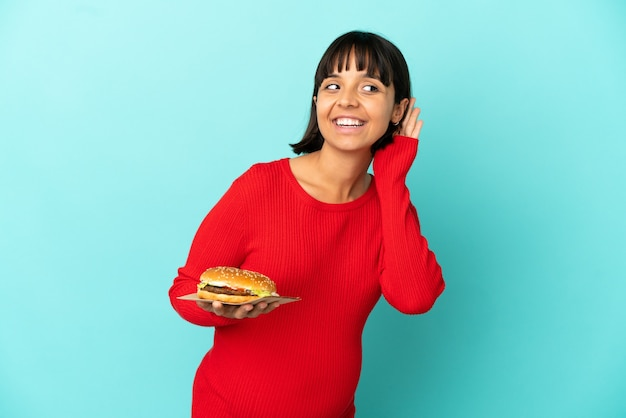 Młoda kobieta w ciąży trzymająca burgera na białym tle, słuchając czegoś, kładąc rękę na uchu