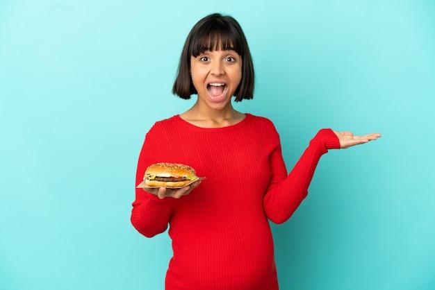 Młoda kobieta w ciąży trzymająca burgera na białym tle ze zszokowanym wyrazem twarzy