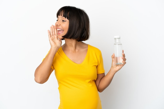 Młoda kobieta w ciąży trzymająca butelkę wody na białym tle krzycząca z szeroko otwartymi ustami