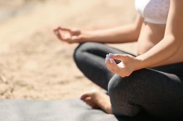 Młoda kobieta w ciąży uprawiania jogi na świeżym powietrzu
