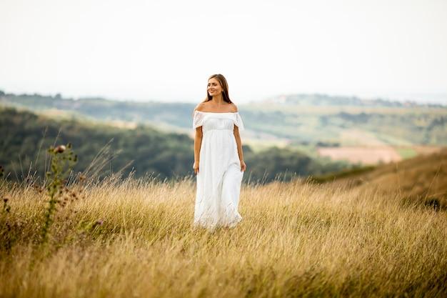 Młoda kobieta w ciąży w białej sukni na letnim polu