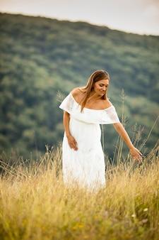 Młoda kobieta w ciąży w białej sukni na polu latem