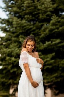Młoda kobieta w ciąży w białej sukni w lesie w letni dzień