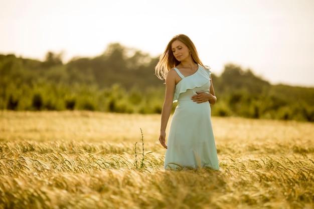 Młoda kobieta w ciąży w niebieskiej sukience w polu latem
