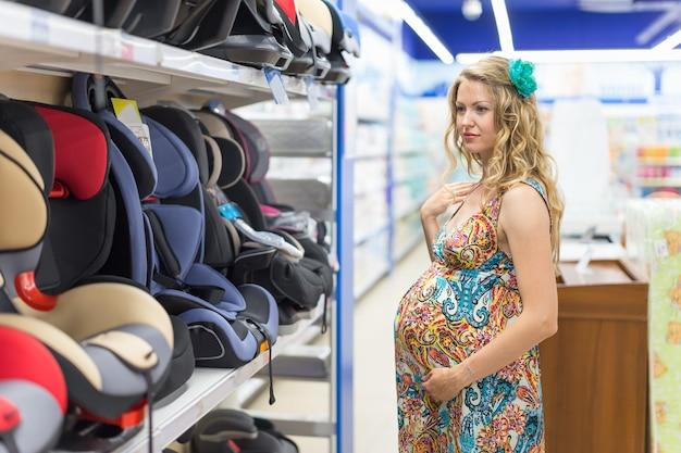 Młoda kobieta w ciąży w sklepie dla dzieci