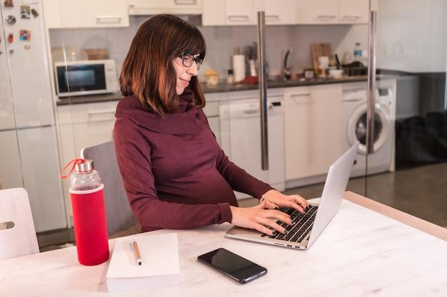Młoda kobieta w ciąży wykonuje telepracę z domu ze względu na trudności w pracy