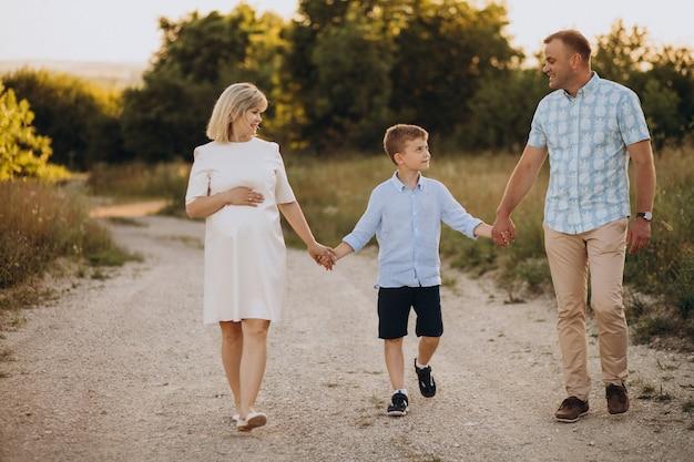 Młoda kobieta w ciąży z mężem i synem na zachód słońca