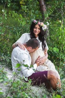 Młoda kobieta w ciąży z mężem z przyrodą na sobie ubranie