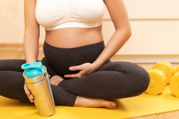 Młoda kobieta w ciąży z shake białka po treningu fitness