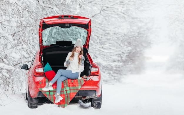 Młoda kobieta w ciepłych ubraniach siedzi w lesie zimą, opierając się na samochodzie i trzymając filiżankę kawy.