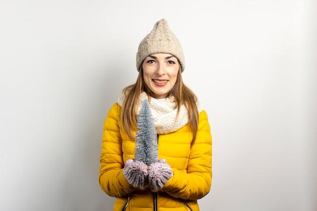 Młoda kobieta w ciepłym kapeluszu i rękawiczkach uśmiecha się na białym tle