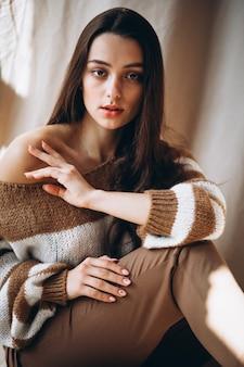 Młoda kobieta w ciepłym swetrze siedzi na ziemi