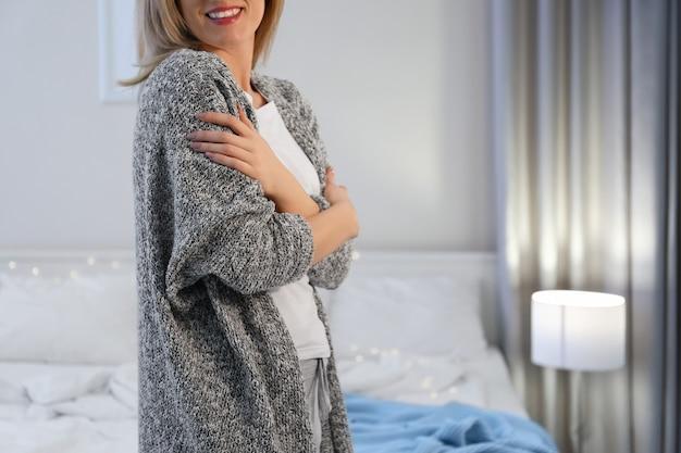 Młoda kobieta w ciepłym swetrze w domu