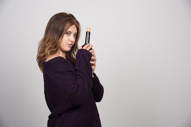 Młoda kobieta w ciepłym swetrze z dzianiny trzyma butelkę wina.
