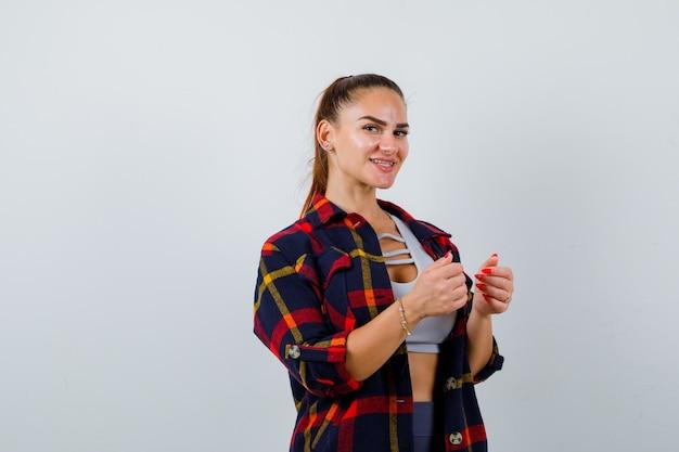Młoda kobieta w crop top, koszula w kratkę, spodnie pozowanie stojąc i patrząc ładnie, widok z przodu.