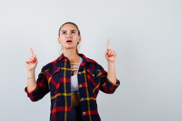 Młoda kobieta w crop top, kraciasta koszula skierowana w górę i patrząc zdziwiona, widok z przodu.