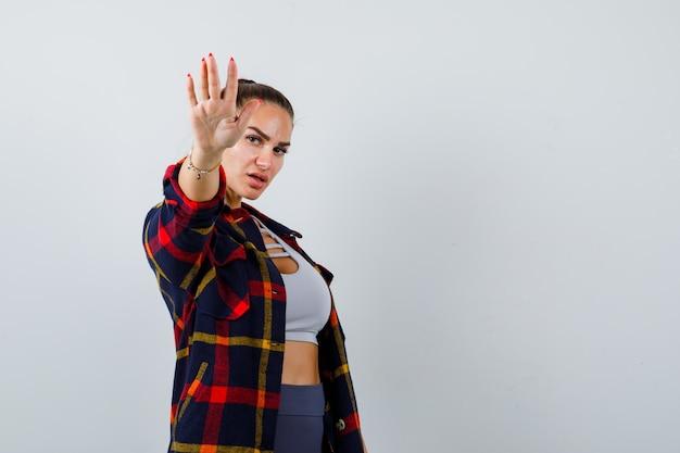 Młoda kobieta w crop top, kraciasta koszula, spodnie pokazujące gest stop i wyglądająca pewnie, widok z przodu.
