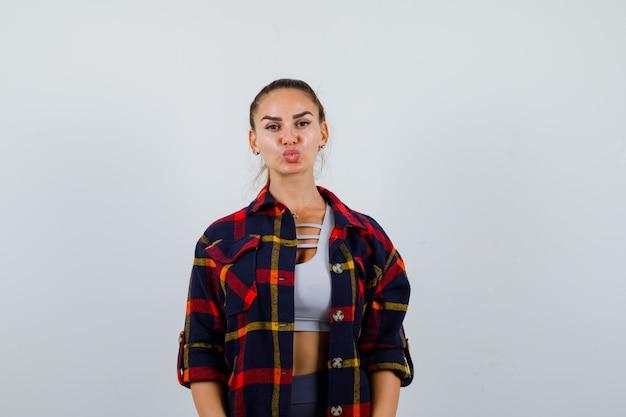 Młoda kobieta w crop top, kraciastej koszuli nadyma usta i wygląda ładnie, widok z przodu.