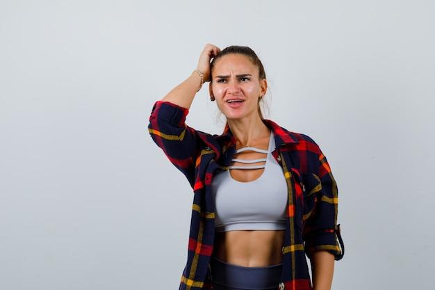 Młoda kobieta w crop top, kraciastej koszuli, spodniach, drapiąc się po głowie i patrząc niezdecydowany, widok z przodu.