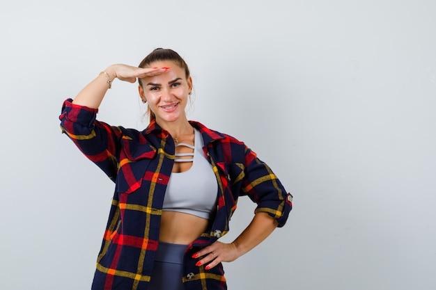 Młoda kobieta w crop top, kraciastej koszuli, spodniach z ręką na głowie, aby wyraźnie widzieć, trzymając rękę na biodrze i patrząc na szczęśliwego, widok z przodu.