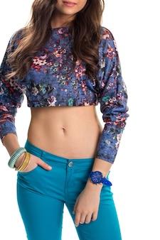 Młoda kobieta w crop top. niebieskie spodnie i kwiatowy top. nowe bransoletki i zegarek. codzienny strój na ciepłe dni.