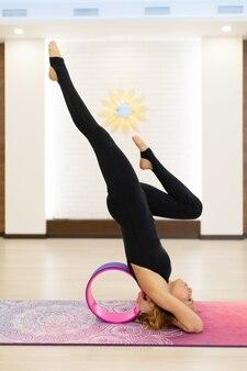 Młoda kobieta w ćwiczeniach jogi sportowej z kołem jogi na siłowni. styl życia rozciągający i wellness.