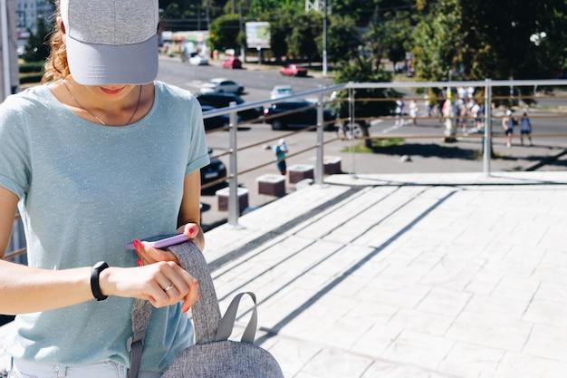 Młoda kobieta w czapce iz plecakiem synchronizuje dane z inteligentnymi zegarkami i telefonem