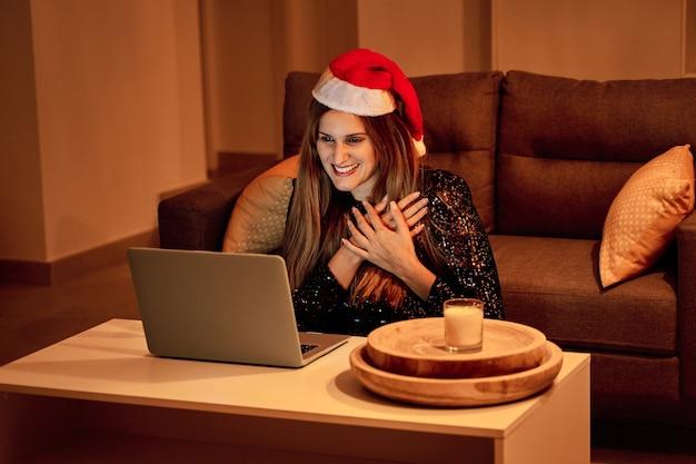 Młoda kobieta w czapce świętego mikołaja prowadzi rozmowę wideo z rodziną, aby świętować boże narodzenie. pojęcie samotności, rozdzielonej rodziny, dystansu społecznego i bożego narodzenia.