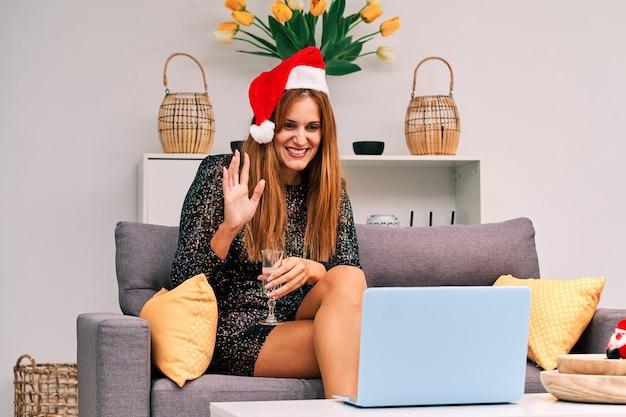 Młoda kobieta w czapce świętego mikołaja prowadzi rozmowę wideo z rodziną, aby świętować boże narodzenie