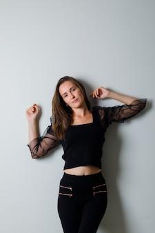 Młoda kobieta w czarną bluzkę i czarne spodnie pozuje z przodu i wygląda uroczo