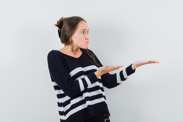 Młoda kobieta w czarnej bluzce i czarnych spodniach trzyma coś wyimaginowanego i wygląda na szczęśliwego