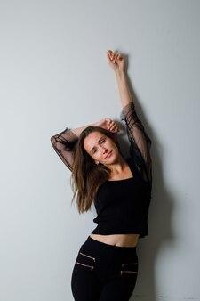 Młoda kobieta w czarnej bluzce i czarnych spodniach trzyma jedną rękę nad głową, drugą w powietrzu i wygląda uroczo