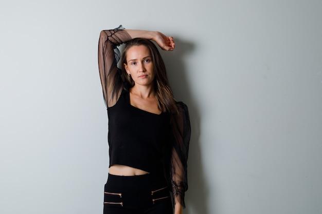 Młoda kobieta w czarnej bluzce i czarnych spodniach, trzymając jedno ramię nad głową i wyglądająca elegancko