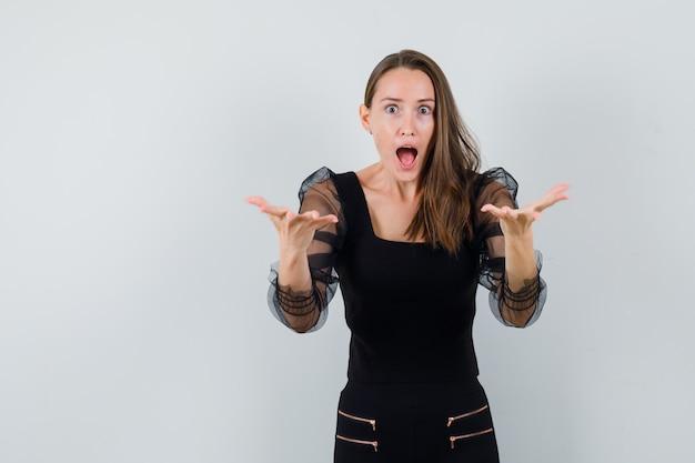 Młoda kobieta w czarnej bluzce i czarnych spodniach wyciąga ręce, żeby coś odebrać i wygląda na zaskoczoną, widok z przodu.