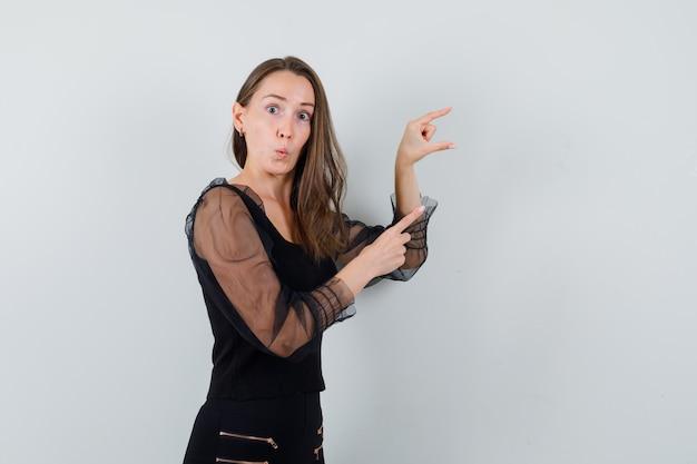 Młoda kobieta w czarnej bluzce i czarnych spodniach wyciągająca jedną rękę, trzymając coś wyimaginowanego i wskazując na to i wyglądając na zaskoczoną, widok z przodu.