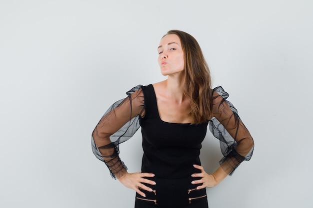 Młoda kobieta w czarnej bluzce mruga podczas wysyłania buziaka i patrzy wesoło