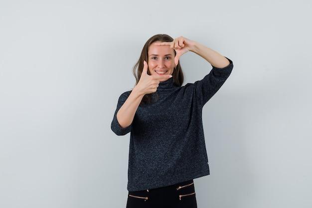 Młoda kobieta w czarnej bluzce pokazując gest ramy i patrząc wesoło