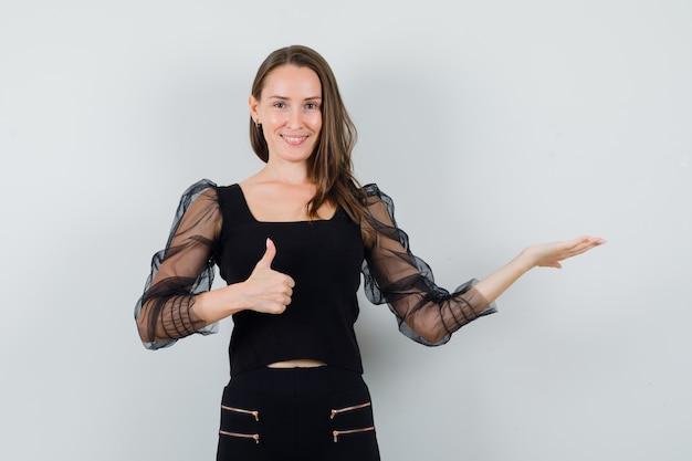 Młoda kobieta w czarnej bluzce pokazuje kciuk do góry, jednocześnie rozkładając otwartą dłoń na bok i patrząc radośnie