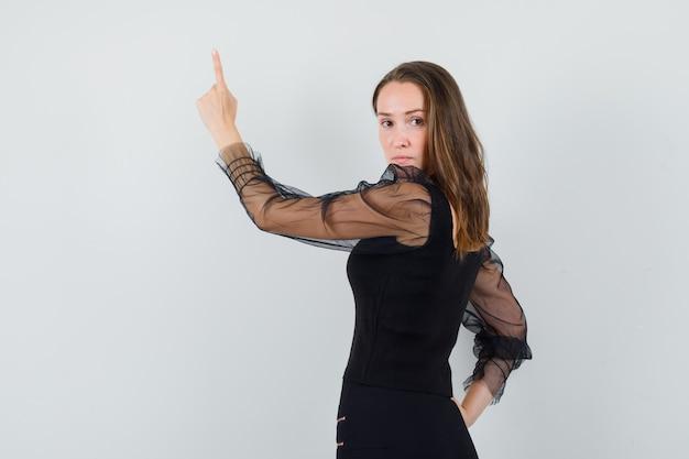 Młoda kobieta w czarnej bluzce skierowaną w górę, patrząc wstecz i patrząc ostrożnie