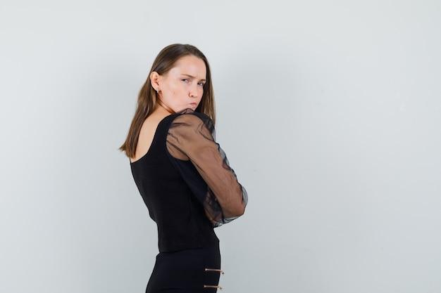 Młoda kobieta w czarnej bluzce stojącej ze skrzyżowanymi rękami, patrząc wstecz i patrząc urażony