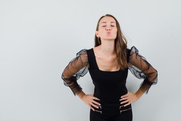 Młoda kobieta w czarnej bluzce, wysyłając pocałunek, trzymając ręce na jej talii i wyglądając na zadowolonego