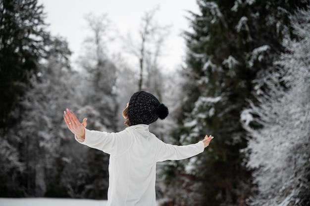 Młoda kobieta w czarnej czapce zimowej stojącej w pięknej śnieżnej przyrodzie z szeroko rozłożonymi rękami.