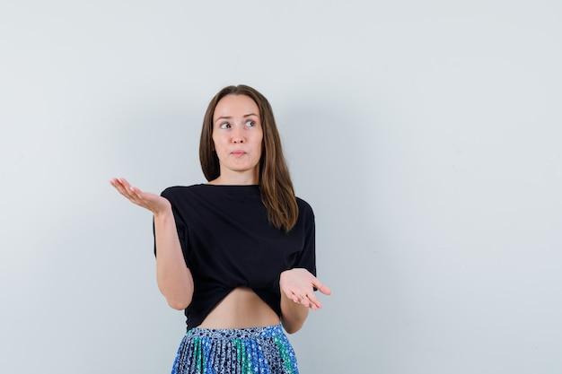 Młoda kobieta w czarnej koszulce i niebieskiej spódnicy podnosząc jedną rękę, trzymając coś, a drugą wyciągając rękę, aby coś otrzymać i wyglądać atrakcyjnie