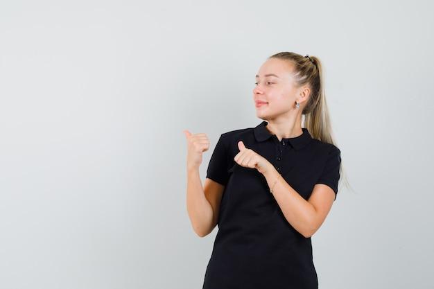 Młoda kobieta w czarnej koszulce, wskazująca na lewą górną część i uśmiechnięta i wyglądająca optymistycznie