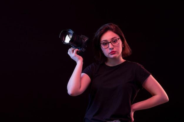 Młoda kobieta w czarnej koszulce z aparatem