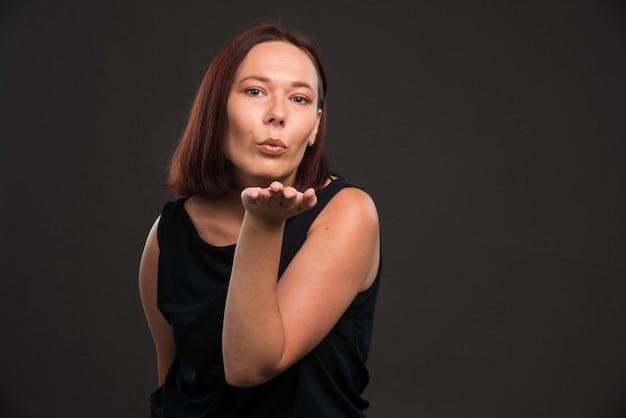 Młoda kobieta w czarnej koszuli dmuchanie buziaka.