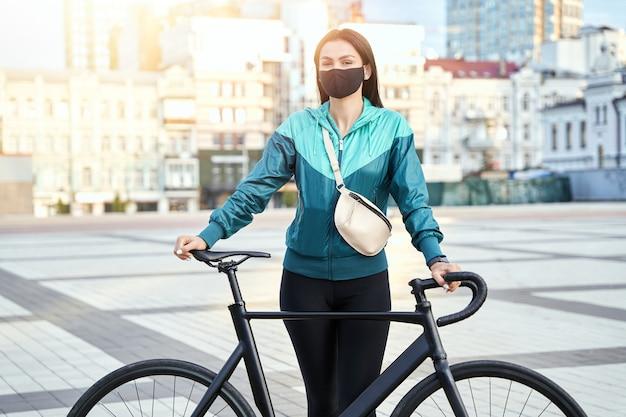 Młoda kobieta w czarnej masce i odzieży sportowej trzyma rower z domami w tle. koncepcja sportu i stylu życia